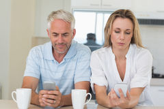 Distant couple sitting at the counter texting and not talking Royalty Free Stock Photo