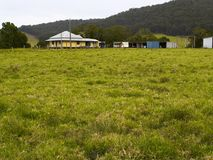 Distant farmhouse. A farmhouse and sheds in front of a distant hill stock photography