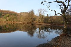 Hill and Trees Reflected in calm blue lake Stock Photography