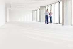 Distant image of business people discussing in empty office Stock Photography