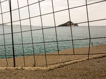 Distant island behind na iron fence Stock Photos
