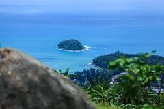 The distant island. A small tropical island. View of the island from the high mountains. The shore is covered with dense vegetation. Tall palm trees by the Stock Images