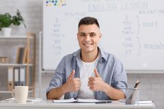 Distant learning language. Smiling young male teacher showing thumbs up and explaining english rules to students