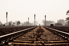 Distant man walking on railway track. A distant, silhouetted man walking on the railway track near Khajuraho train station in India Stock Photography
