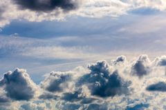 Distant misty backlit cumulus and feather clouds near horizon closeup telephoto shot with polarizing effect. Distant misty backlit cumulus and feather clouds stock photography