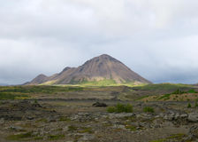 Distant Mountain. Mountain beyond rocky terrain in Iceland Royalty Free Stock Photography