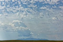 Distant mountain lies in wait. A distant mountain with beautiful clouds and sunlight overhead royalty free stock photo