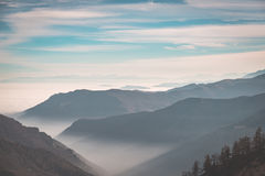 Distant mountain range with fog and mist covering the valleys below.Italian Alps, toned image. Stock Photos