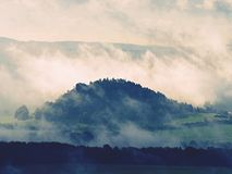 Distant mountain range and heavy clouds of colorful  mist above deep valleys. Early autumnal day in nature park Royalty Free Stock Images