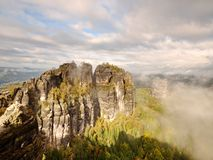 Distant mountain range and heavy clouds of colorful  mist above deep valleys. Early autumnal day in nature park Stock Photo