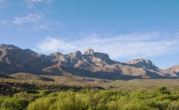 A mountain range with a lush green valley. A distant mountain range in the Sonoran desert with a beautiful blue sky and a lush green valley Stock Photos