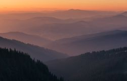 Distant mountain range and thin layer of clouds on the valleys Royalty Free Stock Photography