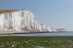 Distant people sunbathing having the white chalk cliffs in the S Royalty Free Stock Image