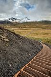 Stairway Descends into Snaefellsjokull National Park in Iceland. A Distant Person Descends the Staircase from Iceland's Saxholl Crater with Snaefellsjokull in Stock Images