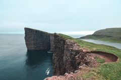 A distant person stands on the Faroe Islands cliffs of Sørvágsvatn Stock Photography