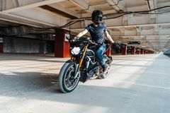 Distant plan of biker in helmet riding motorcycle at parking. Urban background. Front view stock images