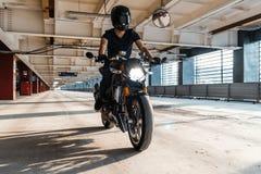 Distant plan of biker riding motorcycle at parking. Urban background stock photos