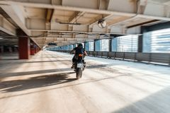 Distant plan of biker riding motorcycle at parking. Urban background. Back view royalty free stock photography