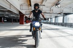 Distant plan of biker riding motorcycle at parking. Urban background. Front view stock image