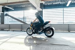 Distant plan of biker riding motorcycle at parking. Urban background. Side view stock image