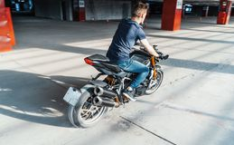 Distant plan of biker riding motorcycle at parking. Urban background. Side view royalty free stock images