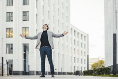 Distant plan of happy man raising his arms while going to or from work. stock photo