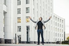 Distant plan of happy man raising his arms while going to or from work. stock images