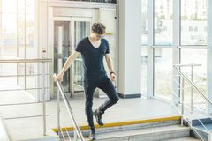 Distant plan of young man going down the stairs at the railway station. royalty free stock photography
