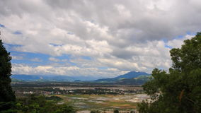 Distant Rice Fields in Water among Mountains Trees at Foreground. Upper panorama of distant rice fields in water and village against mountains and green trees at stock footage