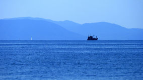 Distant ship sailing in the ocean Royalty Free Stock Images