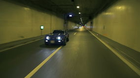 Distant shot of blue Corvette driving at night in a tunnel stock footage