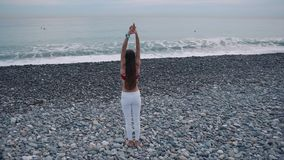 Distant shot of a yoga woman on beach. stock footage
