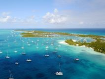 Distant shots of sailboats on the body of water near an island in Exuma