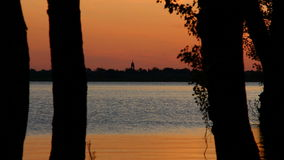 The distant silhouette of church on the sunset sky background. Time of sunset on the lake. In the distance can be seen the silhouette of the church on the sunset stock video footage