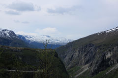 Distant snow covered mountains. Looking to distant snow covered mountains of Norway with clouding skies down a deep gorge of sheer cliffs Stock Image