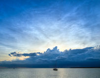 Distant Storm. Yacht returning to marina as a distant storm rages and obscuring the setting sun Stock Photography