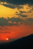 Distant sunset over silhouettes of crests of hills Royalty Free Stock Images