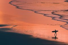 Distant surfer silhouette in the shore at sunset Royalty Free Stock Photos