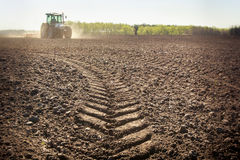 Distant tractor closeup fresh track on wet spring ground Royalty Free Stock Images