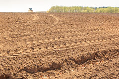 distant tractor leaves fresh track on wet ploughed field Royalty Free Stock Images