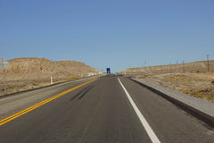 Distant truck  on desert highway Royalty Free Stock Photo