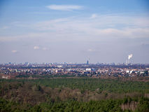 Distant view of the Berlin skyline. Germany, over open countryside showing the topography of the city and industrial chimney belching smoke causing smog Royalty Free Stock Photo