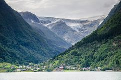 DIstant view of a Buarbreen glacier valley with a small village in front in Odda region, Norway stock image