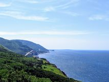 A distant view of the Cabot Trail on Cape Breton Island, Nova Scotia, Canada. The beautiful coastal highway provides amazing view. S of the coastal landscape and stock photos