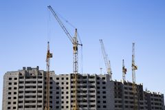 Distant view of a construction site with an unfinished apartment building and several cranes. Clear blue sky serves as a background Stock Images