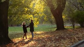 Distant view of elegant couple dancing in the autumn city park in a bright sunlight. No people around. Romantic date stock video footage