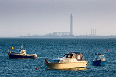 Distant view of Grain power station. Distant view looking towards Grain power station on the Isle of Grain in the Thames Estuary.  In the foreground are three Royalty Free Stock Photo