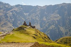 Distant view of Holy Trinity Church in Kazbegi near Stepantsminda view Caucasus mountains in the background royalty free stock photo