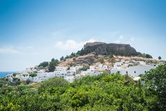 Distant view at Lindos Town and Castle with ancient ruins of the Acropolis on sunny warm day. Island of Rhodes, Greece. Europe.  stock images