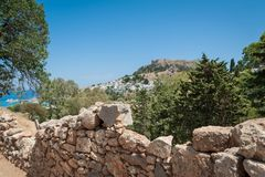 Distant view at Lindos Town and Castle with ancient ruins of the Acropolis on sunny warm day. Island of Rhodes, Greece. Europe.  royalty free stock images